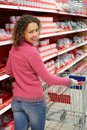 Woman in shop is standing half-turned, smiles Royalty Free Stock Images