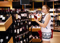 Woman shopping for alcohol in a bottle store wine or other standing front of shelves full of bottles with serious expression Stock Photo