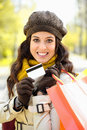 Woman with shopping bags and credit card on autumn fashion trendy showing carrying after buying caucasian brunette shopper Stock Photography