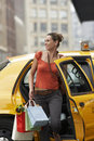 Woman with shopping bags exiting taxi smiling young yellow Stock Photos