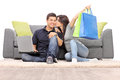 Woman with shopping bags kissing her boyfriend seated by a sofa isolated on white background Royalty Free Stock Photography