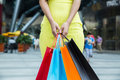 Woman with shopping bags in mall wearing a yellow skirt Stock Photography
