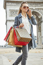 Woman with shopping bags near Arc de Triomphe using cell phone Royalty Free Stock Photo