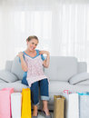 Woman with shopping bags trying out a new top sitting on the sofa Stock Photos