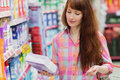 Woman with shopping basket holding product Royalty Free Stock Photo