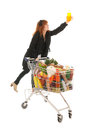 Woman with shopping cart full dairy grocery picking the soap products climbing and isolated over white background Royalty Free Stock Photo