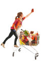 Woman with shopping cart picking food from high cupboard full dairy grocery products glass pot pasta sauce isolated over white Stock Image