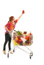 Woman with shopping cart picking food from high cupboard full dairy grocery products glass pot pasta sauce isolated over white Royalty Free Stock Images