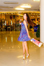 Woman in shopping center beautiful young with bag and a cocktail hands walking through the Royalty Free Stock Photos