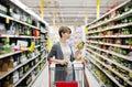 Woman shopping and choosing goods at supermarket Royalty Free Stock Photo