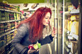 Woman shopping choosing something from a fridge in a supermarket Royalty Free Stock Photos