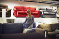 Woman shopping for furniture and home decor young hispanic sofa in store Royalty Free Stock Photos