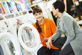 Woman shopping at home appliance supermarket young female seller assistant helps women to choose washing machine in mall Stock Photo