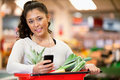 Woman with Shopping List on Phone Royalty Free Stock Photo