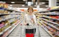 Woman with shopping list pushing cart looking at goods in supermarket Royalty Free Stock Photo