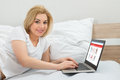 Woman shopping online using laptop happy beautiful in bed Royalty Free Stock Photography