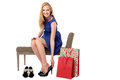 Woman shopping for shoes smiling stylish young sitting on a bench trying on a pair of elegant stilettoes with carrier bags propped Stock Image