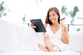 Woman shopping on tablet computer and credit card sitting in sofa smiling happy pretty cheerful asian caucasian shopper Stock Photography