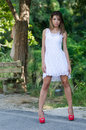 Woman in short white dress lush vegetation as background slim and good looking with shapely long legs and bolt red high heels Royalty Free Stock Image