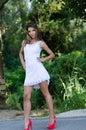 Woman in short white dress, lush vegetation as background Royalty Free Stock Photo