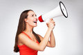 Woman shouting through megaphone casual young over grey background Royalty Free Stock Image