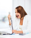 Woman shouting into phone in office Royalty Free Stock Photo