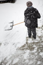 Woman shoveling snow from the sidewalk in front of his house after a heavy snowfall a city Stock Photography