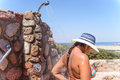 Woman showering after leaving the beach open air shower attached stone wall still wearing her sunhat rid herself adhering sand Royalty Free Stock Photo