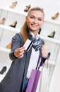 Woman showing credit card in footwear shop with great variety of stylish shoes Royalty Free Stock Images