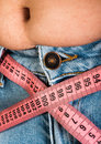 Woman showing fat belly pink tape measure Royalty Free Stock Images