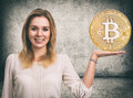 Woman showing Golden Bitcoin coin. Cryptocurrency