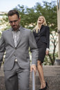 Woman showing power over man in business setting men outdoors Stock Photography