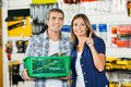 Woman showing something to man in hardware store men holding basket of tools Royalty Free Stock Images