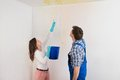 Woman showing water leaking from ceiling to maintenance guy young with bucket damage Royalty Free Stock Photos