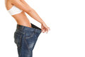 Woman shows her weight loss by wearing an old jeans, isolated on Royalty Free Stock Image