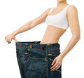 Woman shows her weight loss by wearing an old jeans isolated on Royalty Free Stock Photos