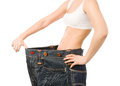 Woman shows her weight loss by wearing an old jeans. isolated on Royalty Free Stock Photo