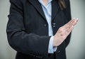Woman signals denial with one hand professional in business suit on grey background Royalty Free Stock Images
