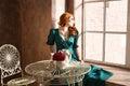 Woman siiting near window vintage interior luxury Stock Photo