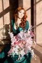 Woman siiting near window vintage interior luxury flowers Royalty Free Stock Photo