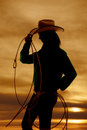 Woman silhouette cowgirl rope a of a with a and hat with a beautiful sunset in the background Stock Photos