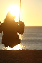 Woman silhouette swinging at sunset on the beach and watching sun Stock Image