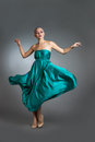Woman in  silk dress waving on wind. Flying and fluttering gown cloth over gray background Royalty Free Stock Photo