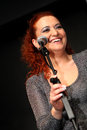 Woman singer holding microphone over dark background Royalty Free Stock Image