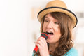 Woman singing with a microphone beautiful wearing hat and red Stock Photography