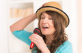 Woman singing with a microphone beautiful wearing hat and red Royalty Free Stock Images