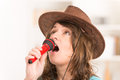 Woman singing with a microphone beautiful wearing hat and red Royalty Free Stock Photo