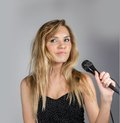 Woman singing in microphone on grey Stock Photos