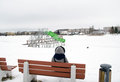 Woman sit bench water cascade playground winter in grey coat on wooden in beach covered with snow and equipment Stock Photos