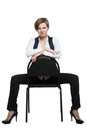 Woman sits astride a chair. arms crossed. dominant Royalty Free Stock Photo